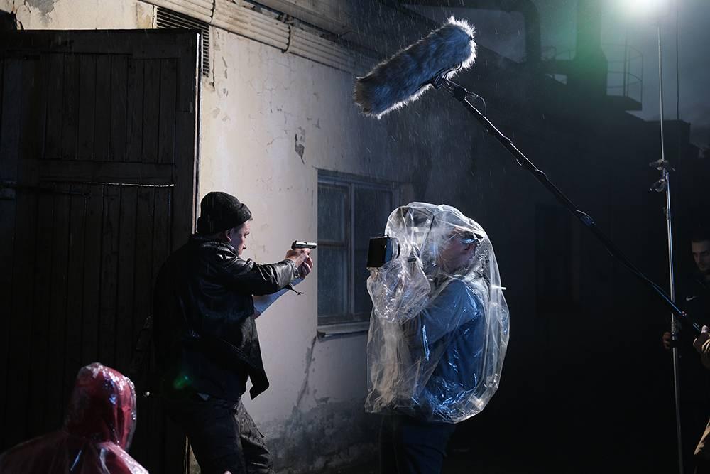 В наших фильмах в некоторых кадрах идет дождь. Длятаких съемок нам пришлось облачить оператора с камерой в пленку. Мохнатое нечто на палке — микрофон, а светящаяся стойка справа — систенд