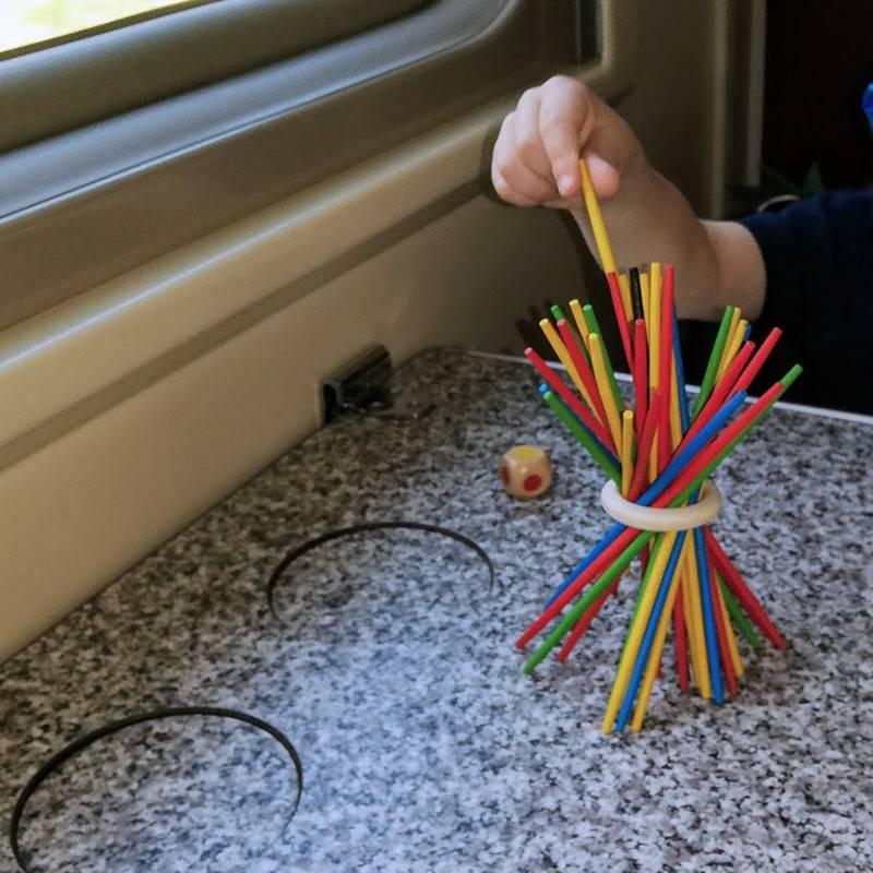 Мы берем с собой простую, но интересную игру «Микадо»: нужно по очереди вытаскивать палочки так, чтобы диск не опустился