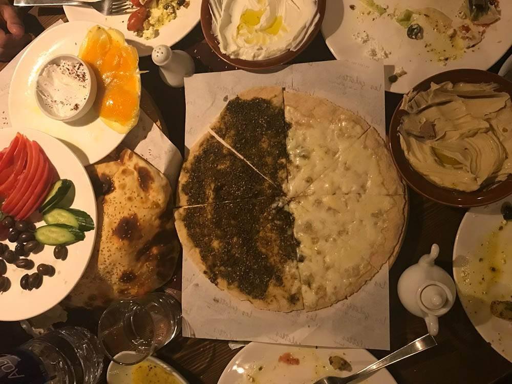 Традиционный ливанский завтрак называется «мануше». Это тонкая лепешка с начинкой сверху. На фото одна половинка с сыром, вторая — с «затаром» (смесь чабреца, специй и кунжута). Стоит около 2,6$ (161<span class=ruble>Р</span>)