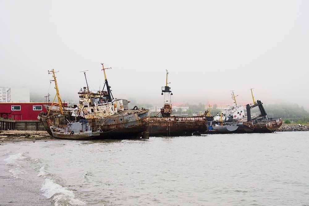 Корабли на пристани микрорайона Марчекан: на палубе видны рыболовные снасти, в рубках горит свет, неподалеку сторожка охранников — то есть люди не боятся выходить на них в море