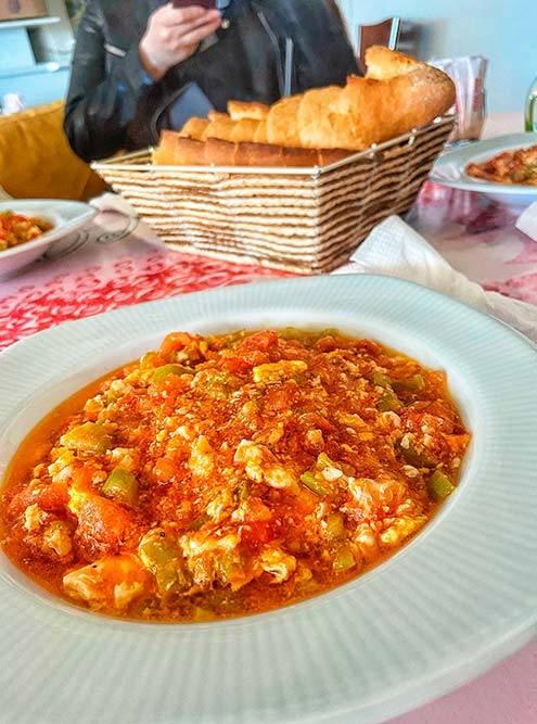 Это менемен — турецкий омлет с овощами и сыром. Идеальное блюдо длязавтрака. Дляприготовления надо обжарить мелко порезанные лук, перец и тертые помидоры и морковь. После добавить на сковороду взбитые яйца. Главный секрет — постоянно все помешивать. В конце посыпать тертым сыром