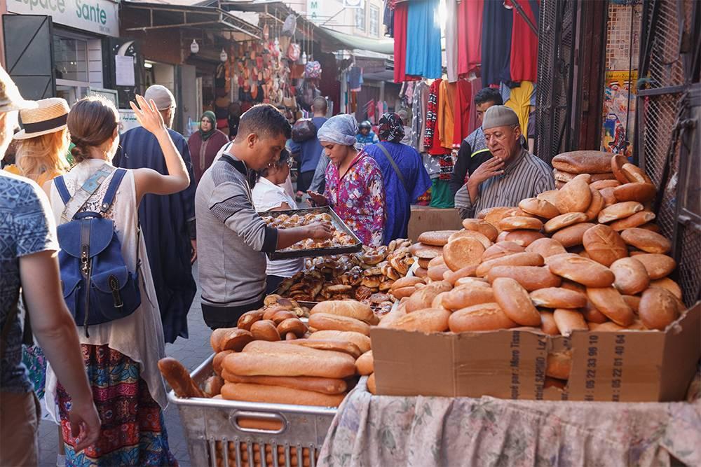 На рынке хлеб и булки лежат на прилавках, ничем не прикрытые