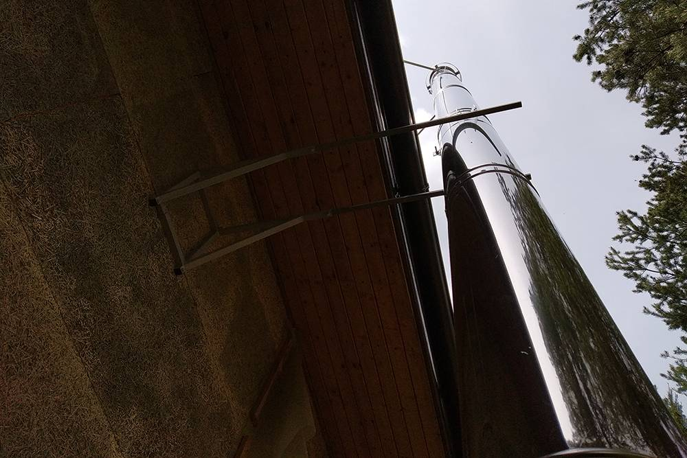 В реальности получилось так: дымоход идет снаружи стены и проходит рядом со свесом крыши