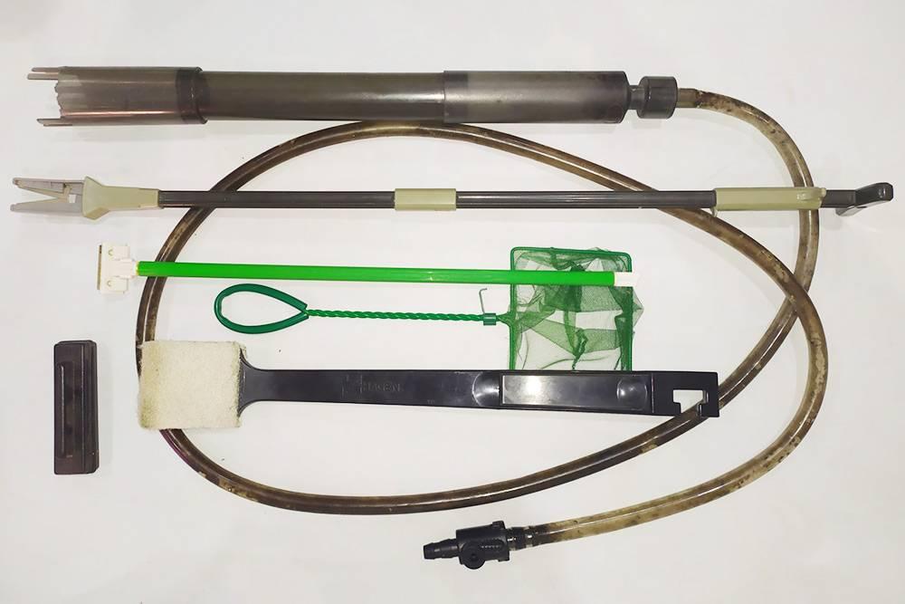 Комплект длянашего углового аквариума на 190л. Сверху вниз: сифон, ножницы длярастений, скребок слезвием, сачок, щетка ислева внизу магнитный скребок
