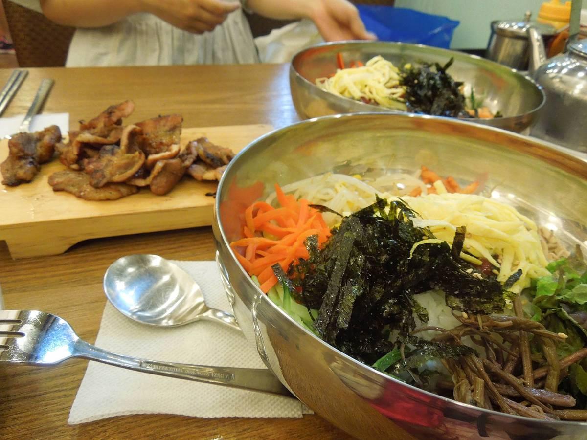 В глубокой тарелке рис с мясов и овощами — пибимпап, а на дощечке мясо, жаренное на гриле, — пулькоги