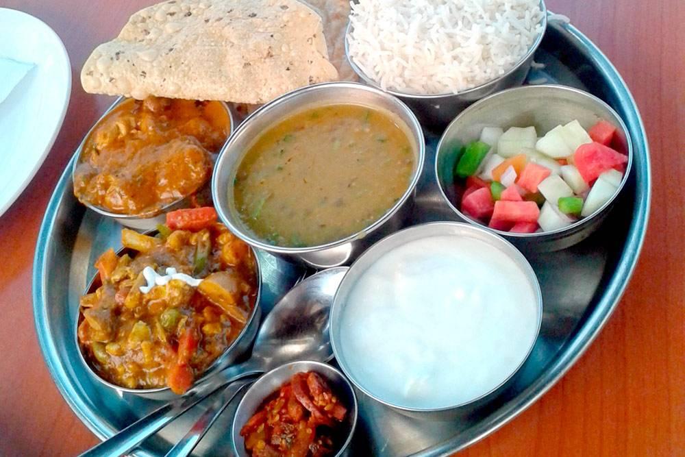 Традиционное индийское тали в ресторане Нью-Дели — рис с лепешками, овощи, соус из бобов, курица и овощи в соусе карри, йогурт. Вкуснее этого я ничего не ела. Блюдо на двоих стоило 240 рупий (232<span class=ruble>Р</span>) — мы еле доели его