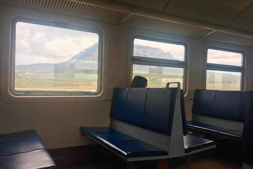 За окном видны горы, вагон полупустой