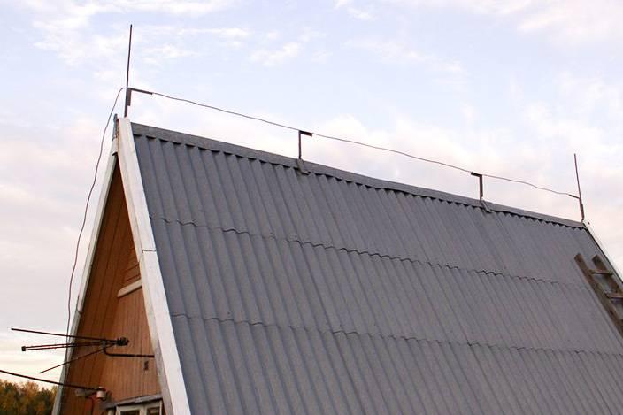Тросовый молниеприемник иногда комбинируют со штыревым: по краям крыши ставят стержни, а между ними натягивают трос. Источник: «Два молотка»