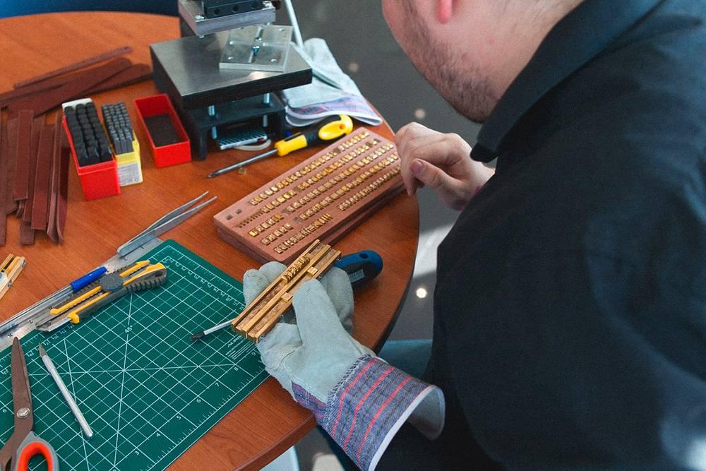 На мастер-классе по созданию кожаных браслетов показывают, как набирать в штамп на двойной оснастке символы для тиснения