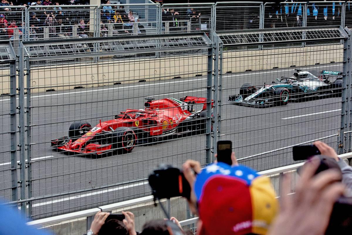 Вид с трибуны «Хазар»: мимо проносятся два четырехкратных чемпиона мира «Формулы-1» — Себастьян Феттель на красной «Феррари» и Льюис Хэмилтон на серебристом «Мерседесе»