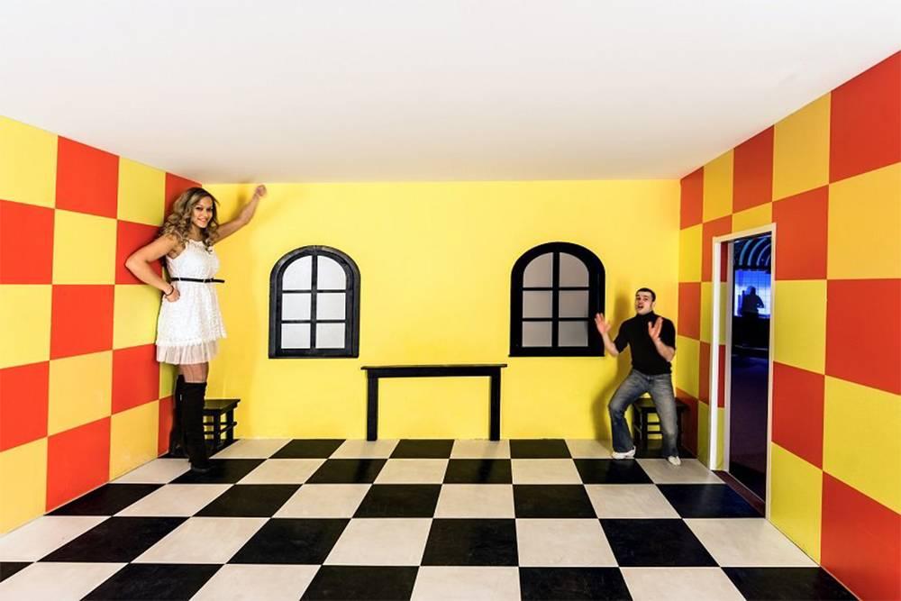 Если заглянуть в комнату Эймса через глазок, то два человека в разных углах будут казаться великаном и карликом. Источник: парк чудес «Галилео»