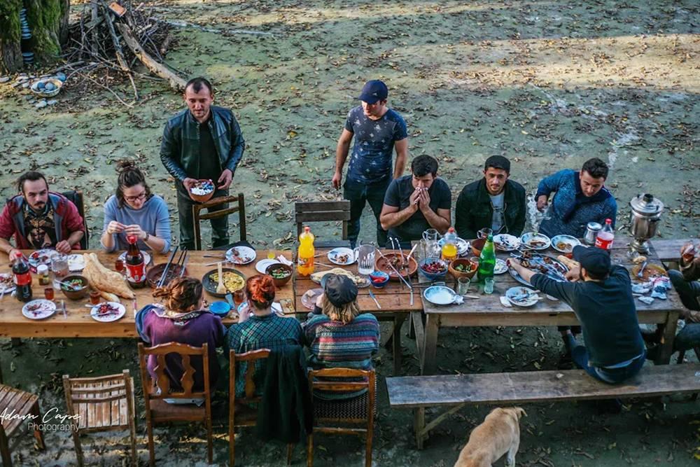 Волонтеры и гости из местных деревень обедают за общим столом