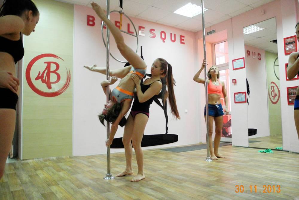 Ученицы выполняют элементы танца на пилоне. Танцоры занимаются в максимально открытой одежде, потомучто зацепиться за шест можно только кожей