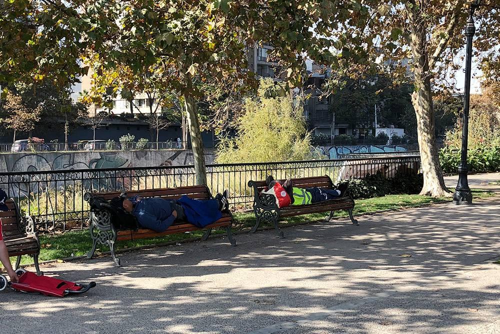 В центре Сантьяго на лавочках спят бездомные