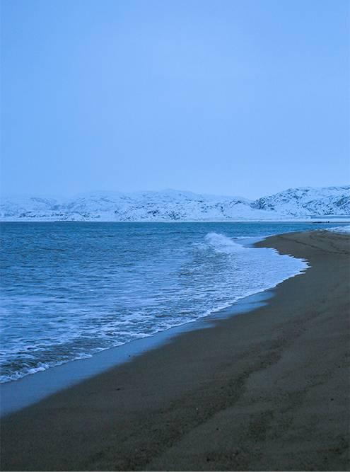 С песчаного пляжа открывается красивая панорама на Лодейную губу — бухту, обрамленную заснеженными сопками