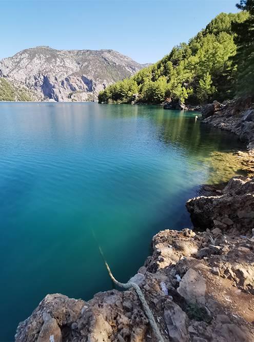 Вода в озере прозрачная и меняет цвет от зеленого до синего в зависимости от того, как падают лучи солнца. Страшно смотреть, как глубоко подводу уходят скалы и веревка