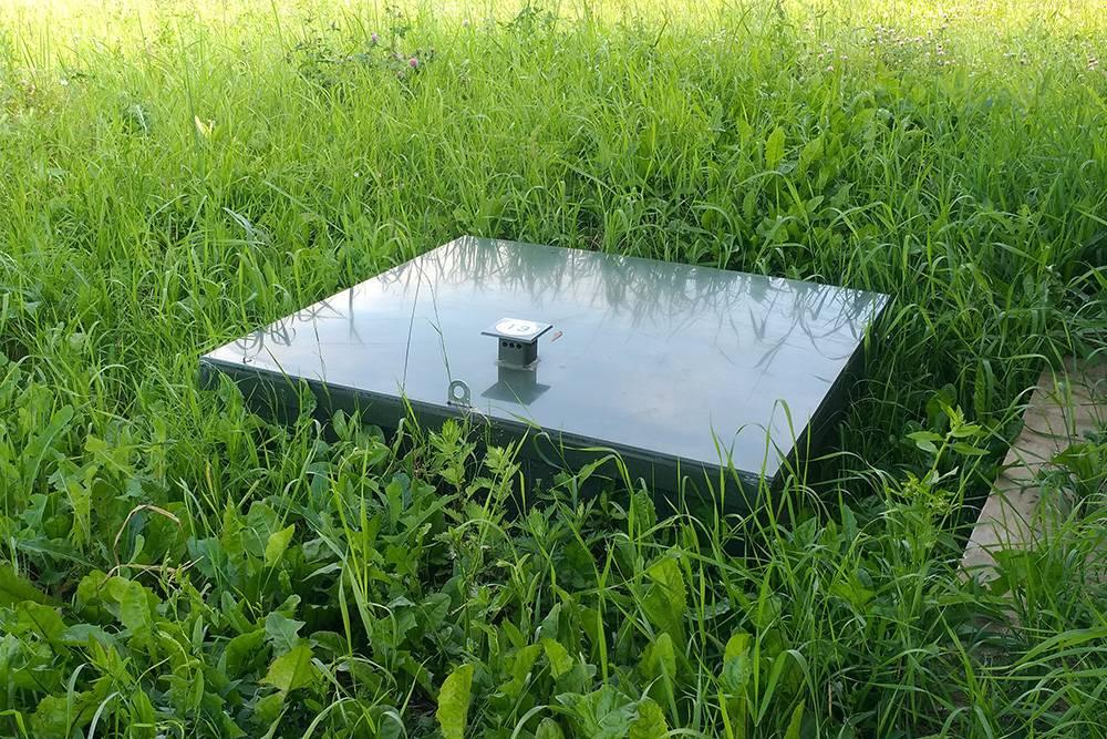 Так выглядит моя станция биоочистки. Зеленая крышка выступает из-под земли на 20 см, но в траве ее почти не видно