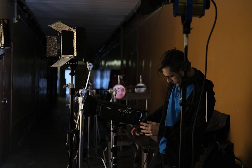Гафер — онже осветитель — настраивает технику перед съемкой