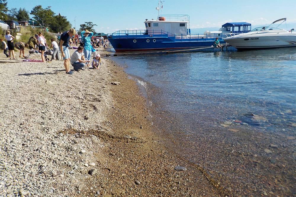 Эту узкую галечную полосу между бетонным парапетом и водой многочисленные туристы используют как пляж. Рядом стихийно швартуются малые суда