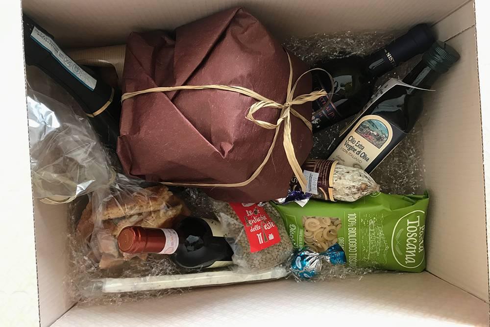Внутри коробки было по бутылке красного вина, десертного вина и просекко, печенье, оливковое масло, макароны, нуга с орехами, чечевица, палка салями и кекс панеттоне. Все продукты произведены в Тоскане