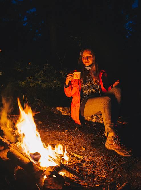 Настя пьет чай возле костра