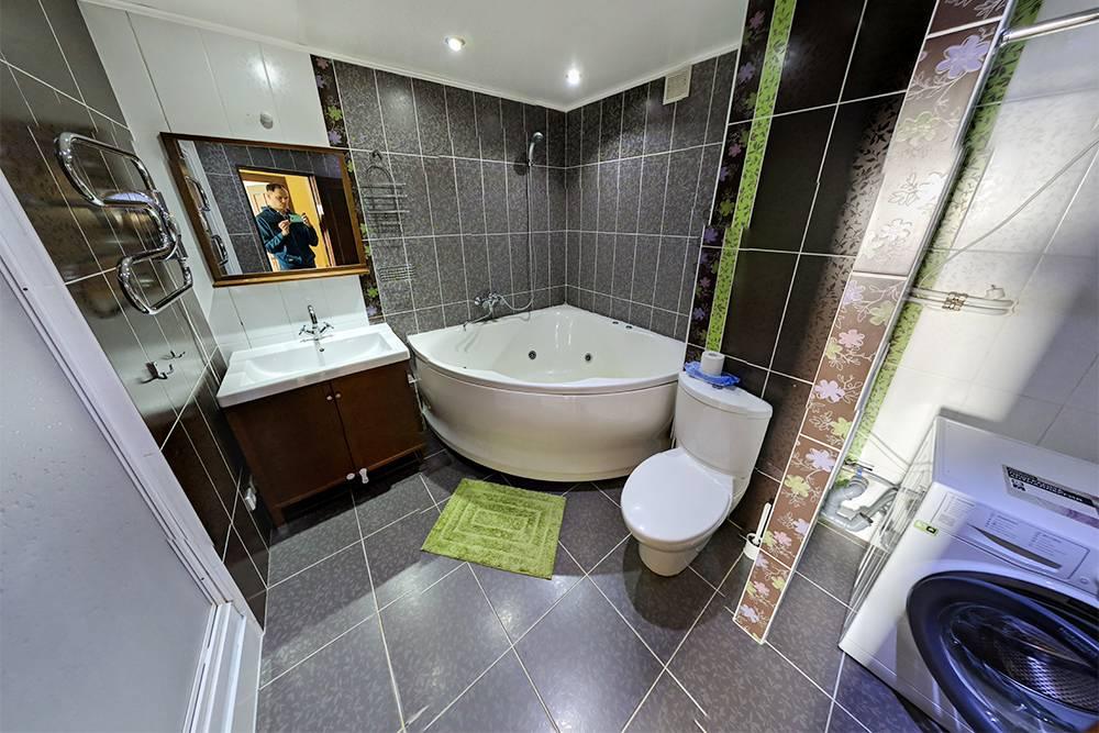 Большая ванная на втором уровне, которая включает в себя туалет, душевую кабину за дверцей и стиралку в нише. На стиралке еще стояла сушилка, но на этой фотографии она уже убрана