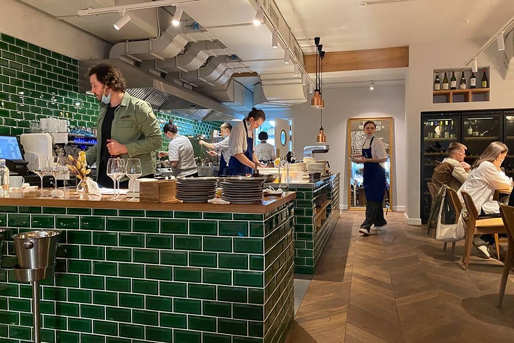 Открытая кухня отделена зеленой плиткой