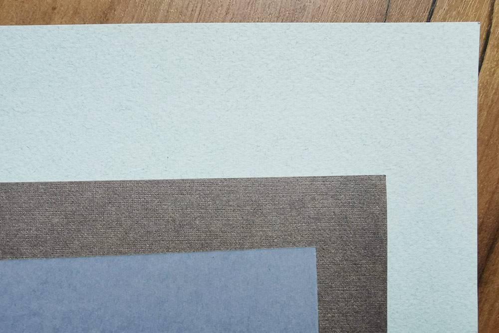 Здесь видно, что у разной бумаги разная фактура. Синий лист гладкий, а голубой — очень фактурный. Я покупаю бумагу разных производителей, чтобы попробовать разные фактуры