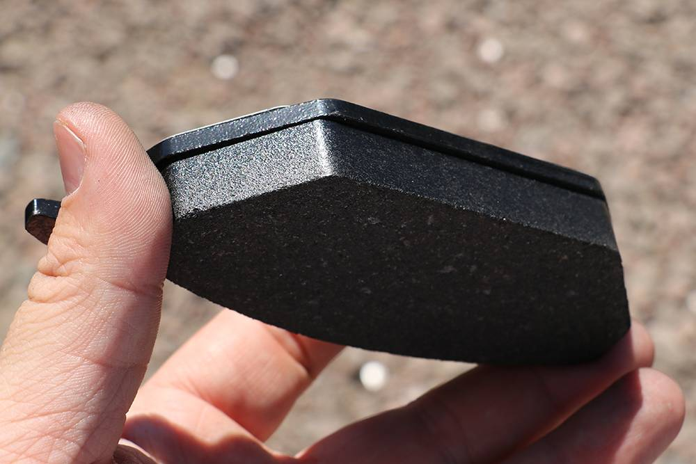 Колодка длядискового тормоза. Верхний слой — металлическая пластина. Все что ниже — фрикционная накладка. Она контактирует с тормозным диском в процессе торможения