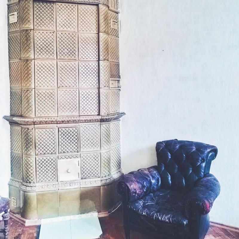 Кожаное кресло — один из экспонатов. Некоторым предметам мебели более 100лет. Еще в коммуналке есть старинный камин и изящная лепнина на потолке