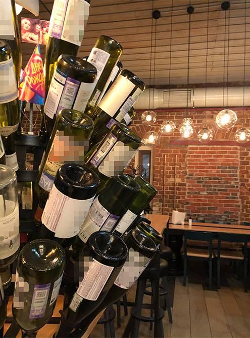 На барной стойке стоит импровизированная елка из винных бутылок