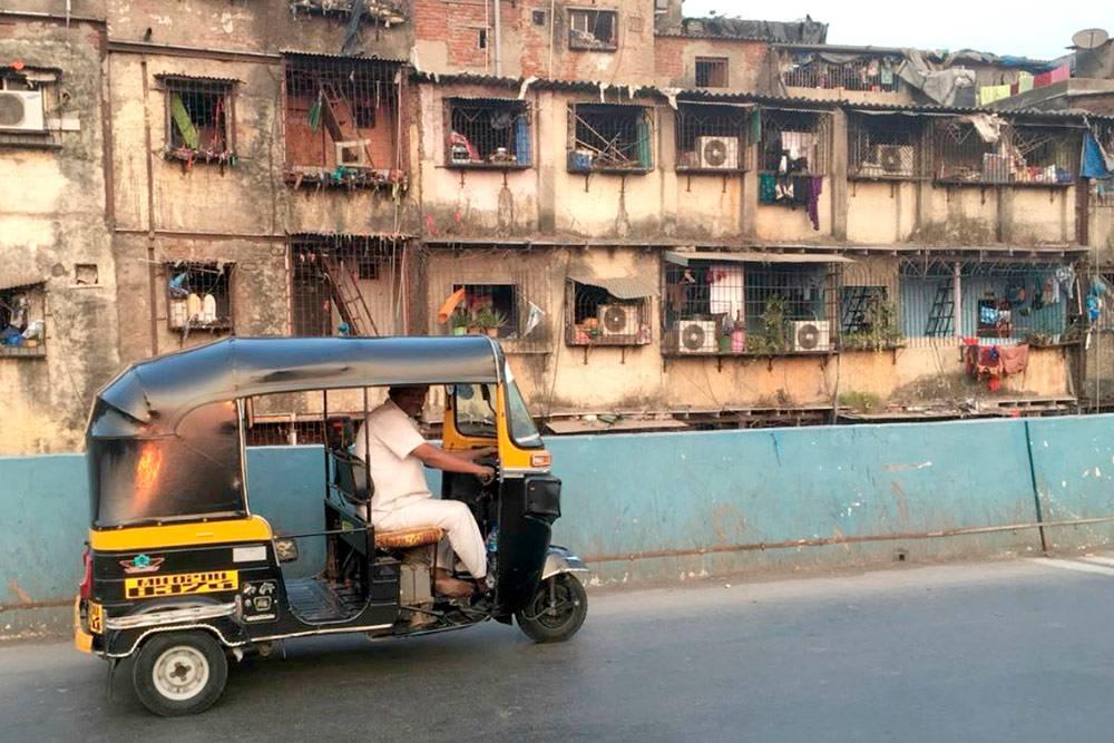 Рикша на фоне трущоб в Мумбаи. Рикшей называют и трехколесное транспортное средство, и водителя