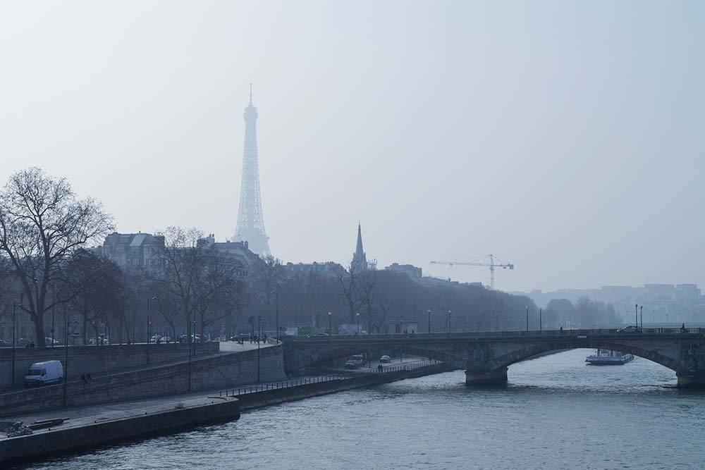 На небе ни облачка, но башня скрыта в легкой дымке — это и есть парижский смог