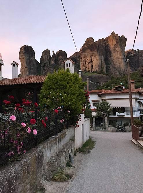 Типичная Каламбака: невысокие домики с черепичными крышами и кусты роз на фоне скал