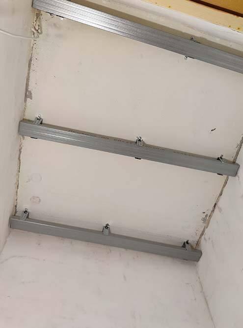 Таккак потолок кривой, гипсокартон необходимо прикрепить на металлические профили: с их помощью можно создать ровную плоскость. К томуже они создают зазор дляпроводов от ламп