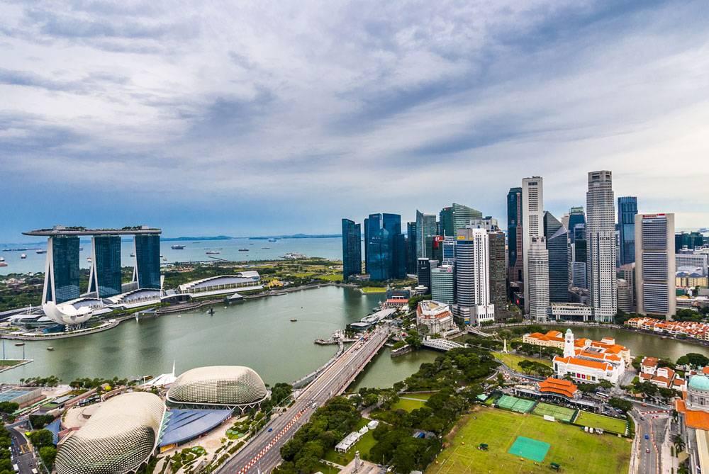Все разнообразие Сингапура на одной фотографии: бурная растительность, стеклянные небоскребы, колониальные кварталы, жилые здания, туристические аттракционы и, конечно, море с сухогрузами и танкерами