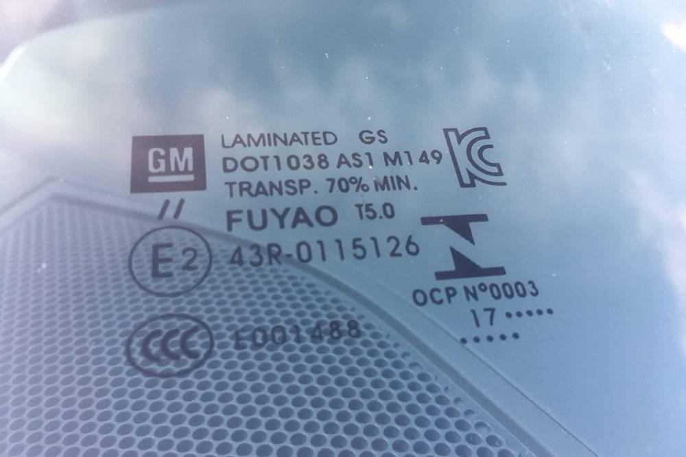 На стекле есть данные о сертификации, значок производителя автомобиля. В этом случае — «Дженерал Моторс». Цифра17 в нижней строчке — год производства стекла. Иногда пишут только последнюю цифру