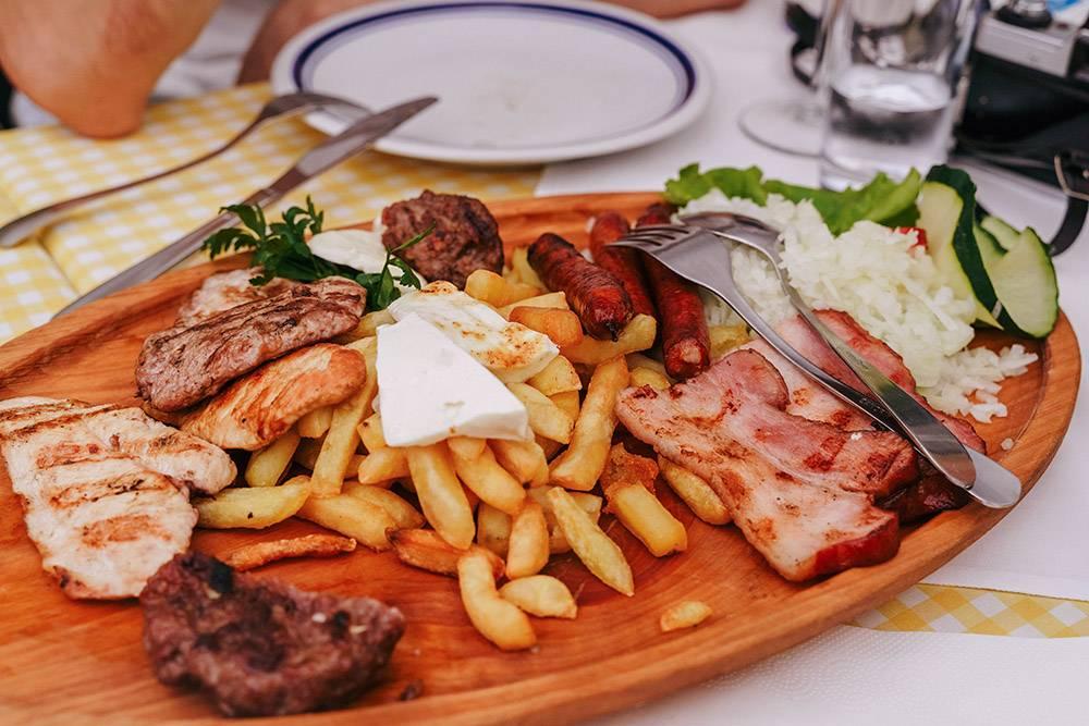 Тарелка мясных закусок: колбаски, бекон, кусочки плескавицы и чевапчичи. В дополнение — картошка, козий сыр и много лука