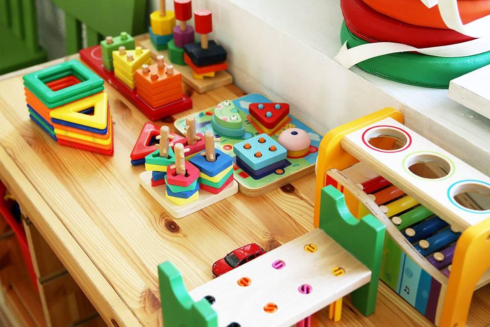 Большинство игрушек в садиках деревянные. Они развивают навыки конструирования, фантазии и мелкой моторики. Готовых игрушек мало, зато много конструкторов, из которых дети могут собрать что угодно, и природных материалов — шишек, листьев, палочек. Для сюжетно-ролевых игр дети сами вырезают игрушки из картона: например, для игры в магазин или парикмахерскую