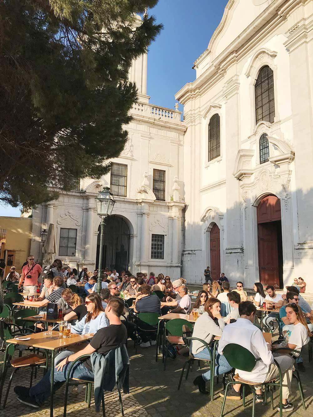 Типичный Лиссабон: церковь, площадь, кафе, прекрасная погода, все пьют пиво и общаются, а с другой стороны открывается великолепный вид на город с холма