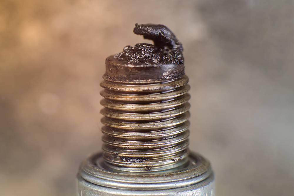 Свеча в моторном масле. Двигатель, из которого ее выкрутили, требует серьезного ремонта или замены. Источник: Chaowalit jaiyen / Shutterstock