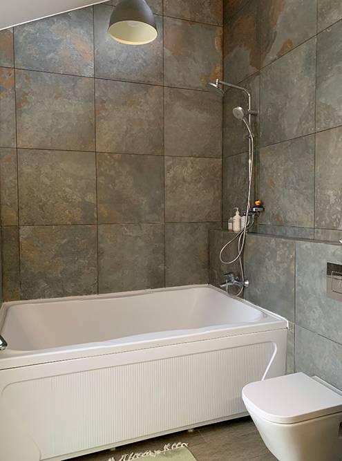 Тамже расположена ванная. Длянее мы выбрали плитку поднатуральный камень