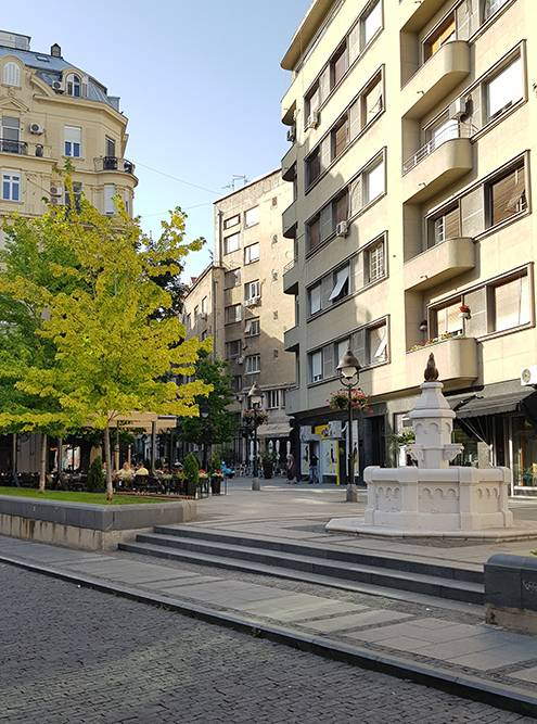 На площади у фонтана с петухом тихо и нет толп, только люди неспешно пьют кофе