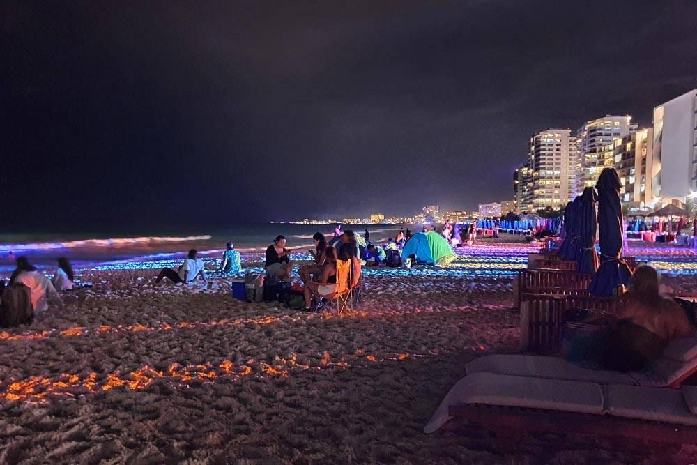 Пляж Канкуна в новогоднюю ночь заполнен туристами. В Hard Rock Cafe играет музыка, все веселятся и отмечают, организовав пикник, некоторые даже с палатками. Здесь спокойнее, чем на площади возле клубов