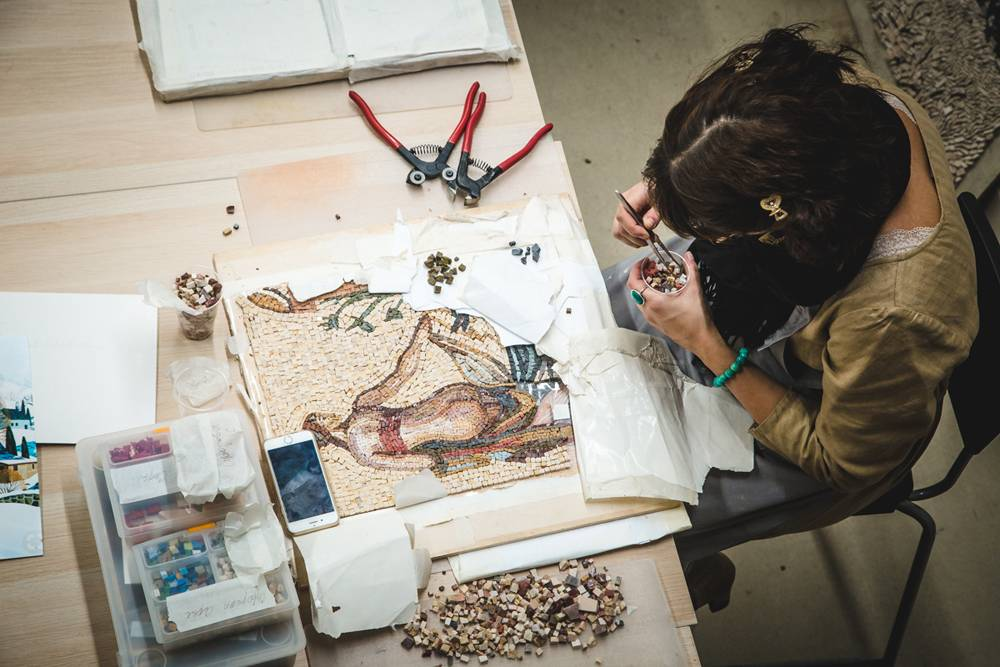 Ученица работает над мозаикой из камня в классическом римском стиле