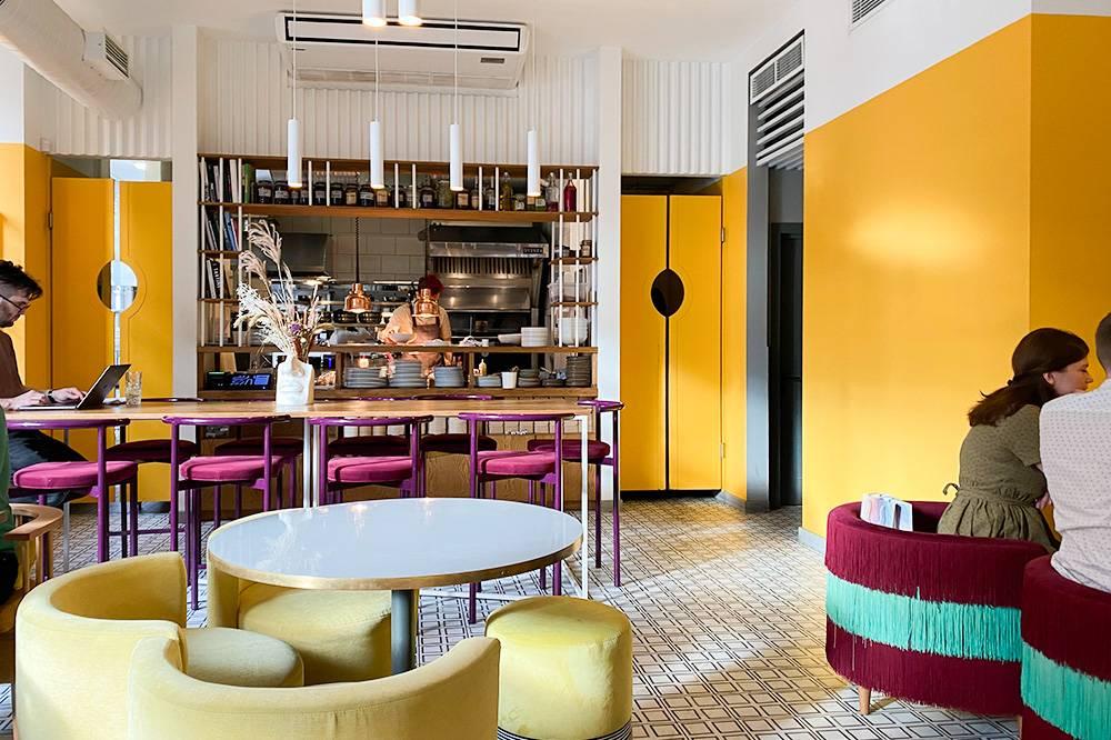 Основная зона с круглыми столами, мягкими креслами и яркими цветами