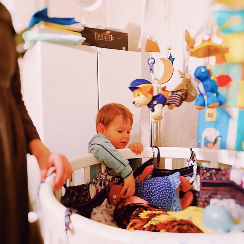 На этой фотографии я стою рядом с кроваткой не случайно: пока сын гладит сестру по голове, я слежу, чтобы он не нажал ей на родничок и случайно не ударил игрушками