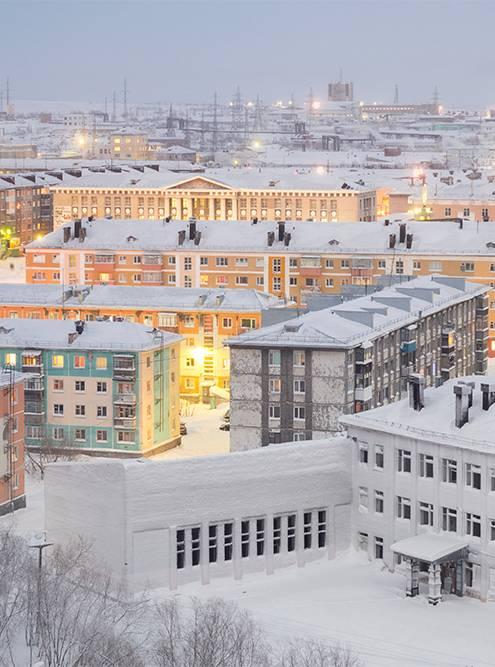 Контрасты Воркуты: заброшенная школа на переднем плане, пестрые жилые пятиэтажки и здание Горно-экономического колледжа с портиком и колоннами
