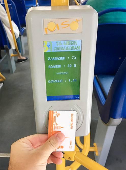 Дляоплаты проезда в автобусе нужно приложить транспортную карту к терминалу у входа. На экране написано: маршрут7а, тариф 30 тетри, баланс 1,6 лари