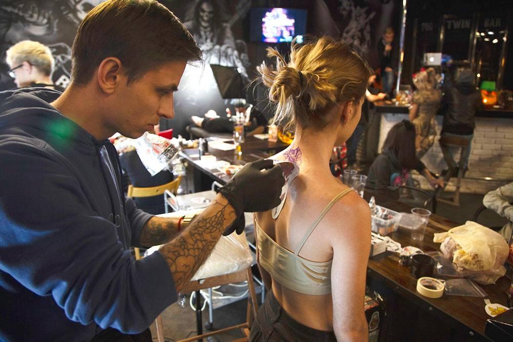 На Walking Night2018 мастер Илья переносит эскиз будущей татуировки на кожу посетительницы